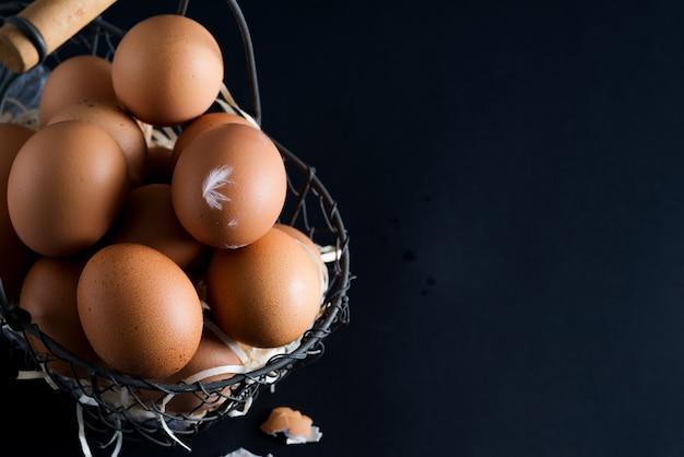 Panier avec bouchent les œufs de poule naturels frais de la ferme sur fond noir. ferme écologique