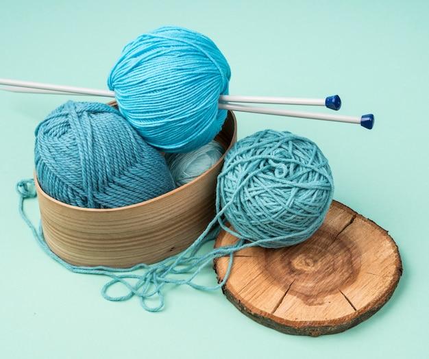 Panier avec des boules de laine colorées et des aiguilles