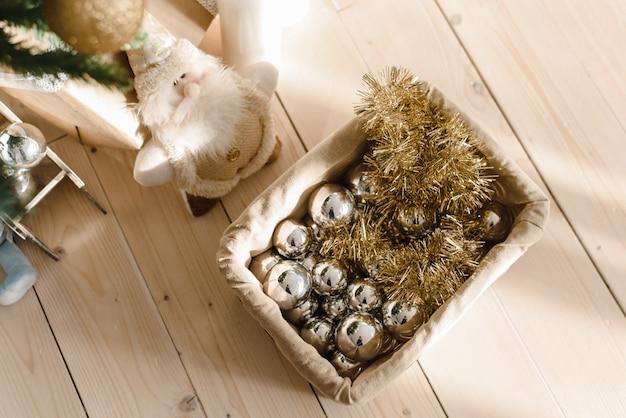 Panier avec des boules de noël et des jouets sous le sapin de noël. préparation pour décorer le sapin de noël. boules d'argent et d'or, guirlandes avec boîte sur un plancher en bois