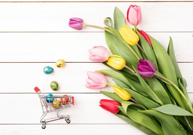 Panier avec bouquet coloré de tulipes sur fond de bois blanc