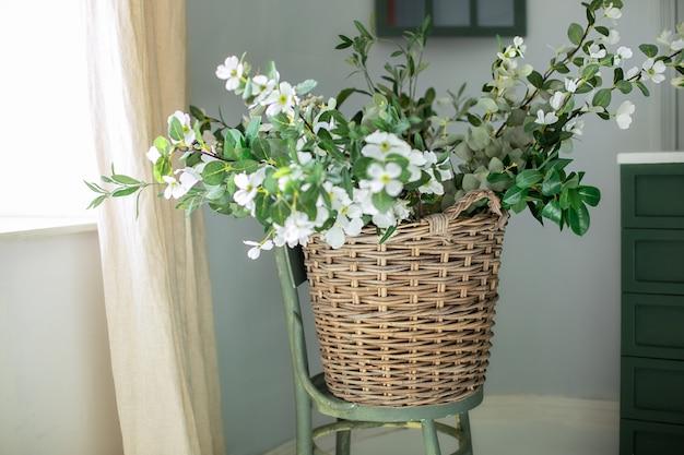 Panier avec bouquet de fleurs blanches sur une chaise en bois près du mur
