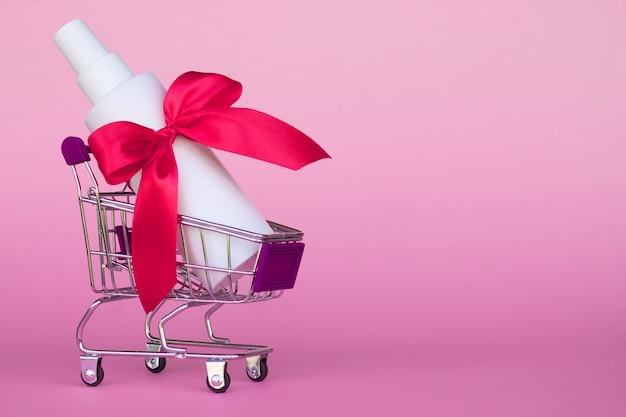 Panier avec bouteille cosmétique avec ruban rouge vif sur fond rose, copiez l'espace.