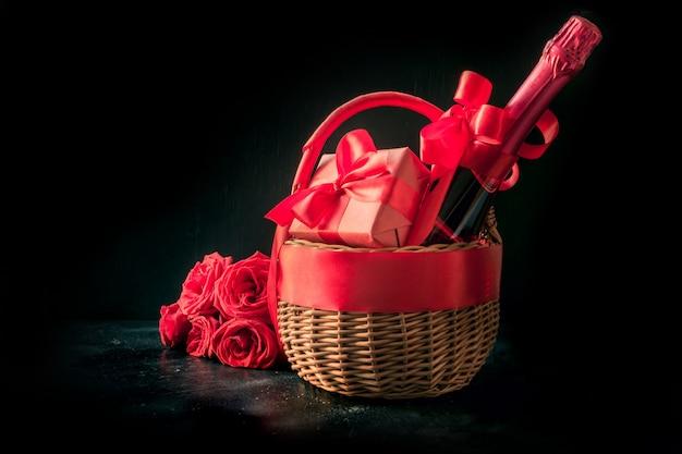 Panier cadeau, bouquet de roses rouges, bouteille de vin mousseux sur fond noir.