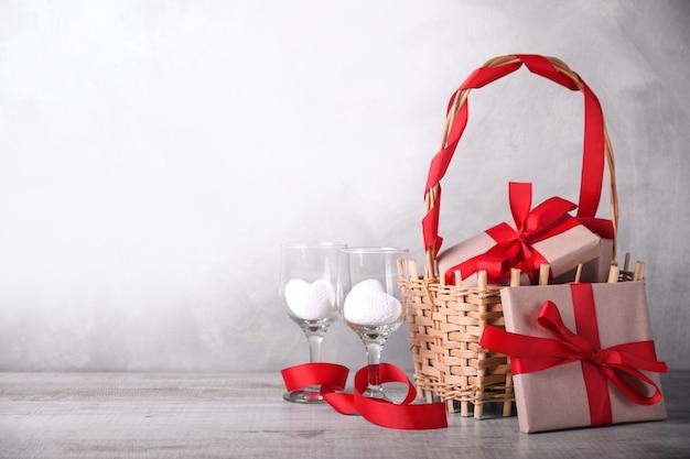 Panier avec des cadeaux et deux verres à vin