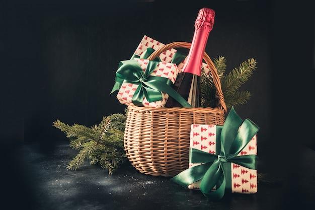 Panier de cadeaux de noël avec du champagne et des cadeaux sur fond noir. espace pour vos salutations. carte de voeux