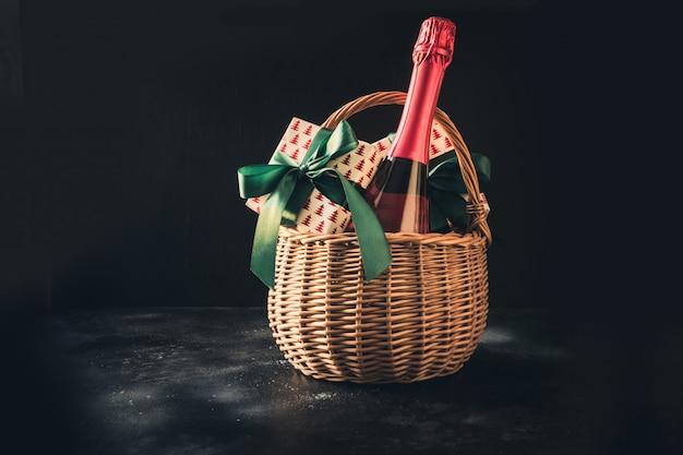 Panier de cadeaux de noël avec du champagne et des cadeaux sur fond noir.
