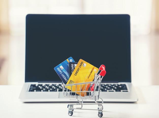 Panier et carte de crédit avec ordinateur portable sur le bureau