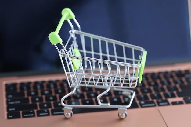 Panier sur le clavier de l'ordinateur portable. vente en ligne dans le concept de magasins en ligne