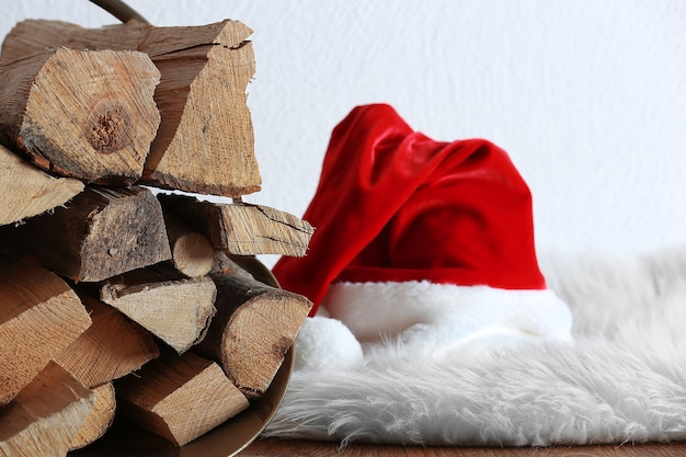 Panier avec du bois de chauffage et un chapeau de père noël sur le sol contre un mur blanc, gros plan