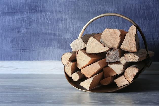 Panier avec du bois de chauffage sur le sol contre une surface texturée
