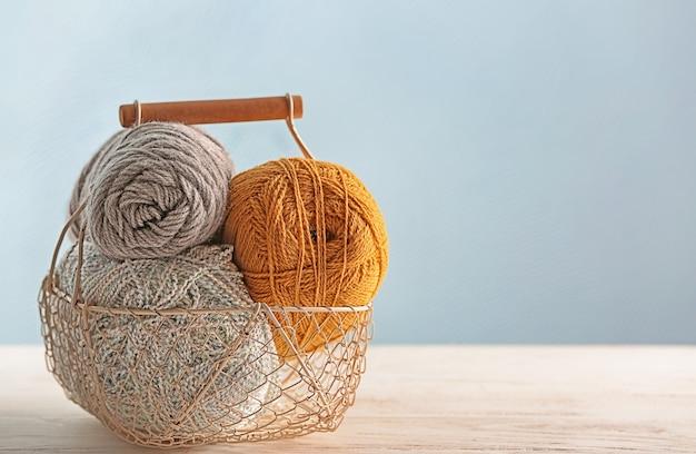 Panier avec du fil à tricoter sur la table contre un arrière-plan de couleur