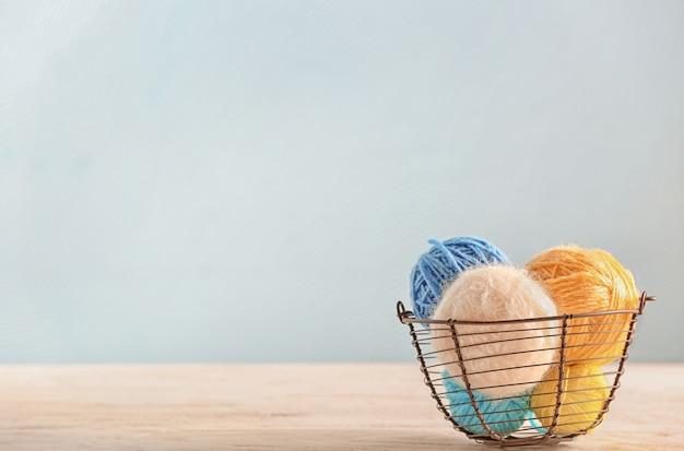 Panier avec du fil à tricoter sur table avec espace copie
