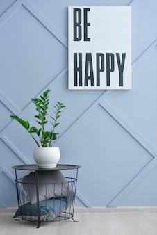 Panier élégant avec oreillers et plante d'intérieur près du mur gris