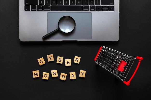 Panier d'épicerie mots pour ordinateur portable cyber lundi fabriqué à partir de lettres en bois et loupe sur fond noir