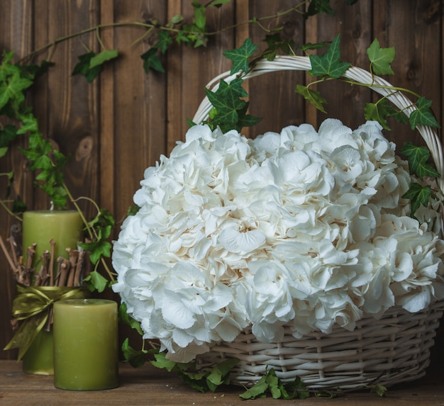 Panier de fleurs blanches comme neige avec des bougies vertes autour