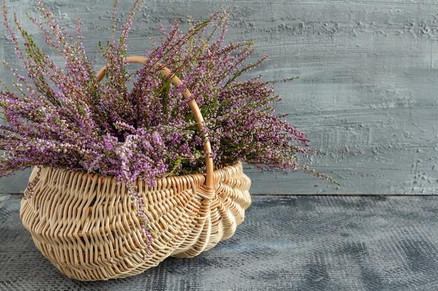 Panier avec des fleurs sur fond de béton bruyère lilas