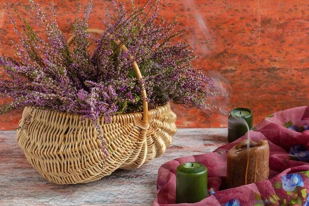 Panier avec des fleurs sur fond rouge et blanc, bruyère lilas et bougies atmosphériques