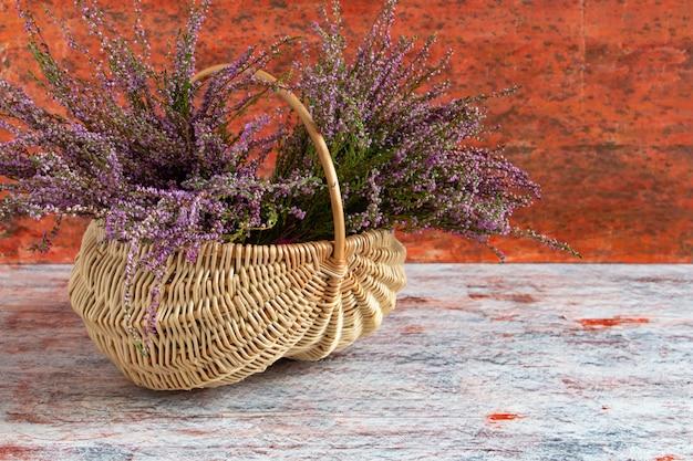 Panier avec des fleurs sur fond rouge et blanc lilas heather copy space