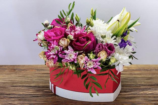 Un panier de fleurs en forme de coeur sur une table en bois