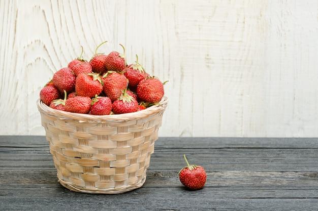 Panier de fraises mûres sur un tableau noir, fond en bois. espace pour le texte
