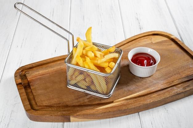 Panier de frites avec du ketchup sur un bureau en bois