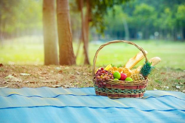Panier de fruits frais comme ananas, pomme, pain, orange, banane sur la carte dans un parc public, concept de santé et de régime alimentaire propre.