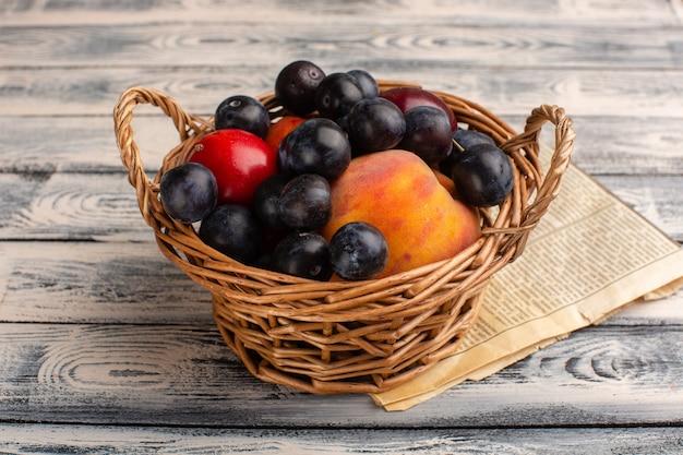 Panier avec fruits prunellier pêches sur bois gris
