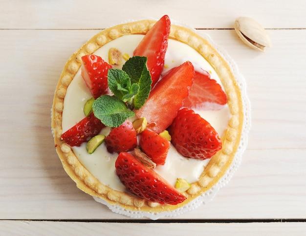 Panier à gâteaux avec fraises, pistaches, crème au beurre et menthe