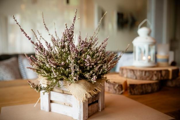 Panier avec heather sur la table.heather dans un panier. fleurs bruyères roses et violettes, bruyère dans une boîte en bois, plantes d'automne et lanterne. maison de campagne. décorations saisonnières