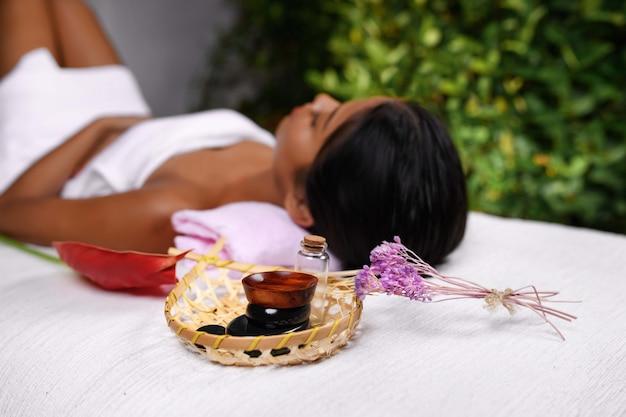 Un panier avec des huiles aromatiques et un brin de fleur. fille interraciale dans une serviette sur une table de massage