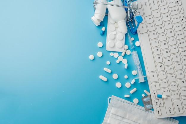 Panier jouet avec médicaments et clavier. pilules, plaquettes thermoformées, bouteilles médicales, thermomètre, masque de protection sur fond bleu. vue de dessus avec place pour votre texte