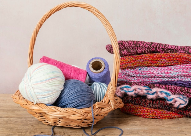Panier avec de la laine et des aiguilles à tricoter