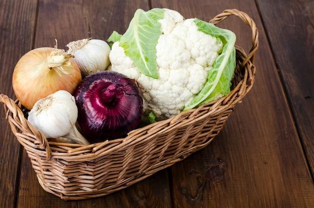 Panier de légumes bio, chou-fleur, oignon, ail. produits de la ferme.