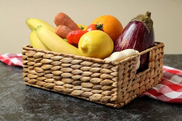 Panier avec des légumes et des fruits sur un torchon sur une table smokey noire
