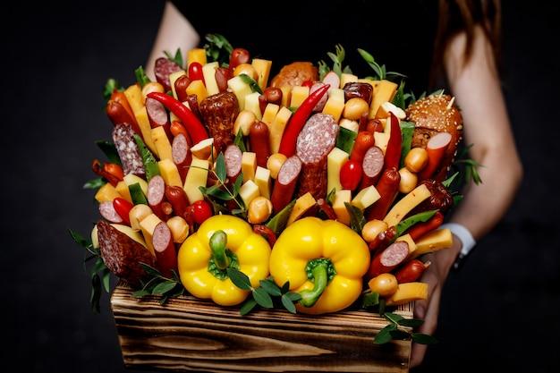 Panier avec légumes et saucisses dans les mains des filles.
