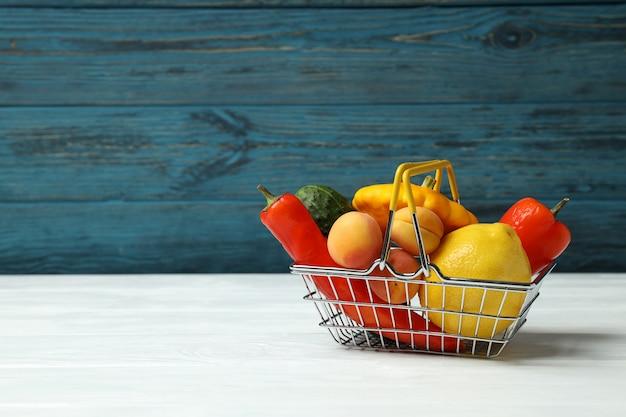 Panier de magasin avec légumes et fruits sur table en bois