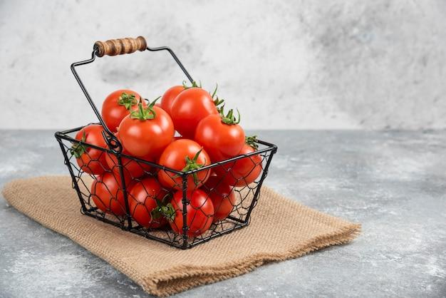Panier en métal de tomates fraîches bio sur marbre.