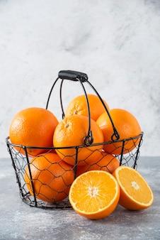 Un panier noir métallique plein de fruits orange juteux sur table en pierre.
