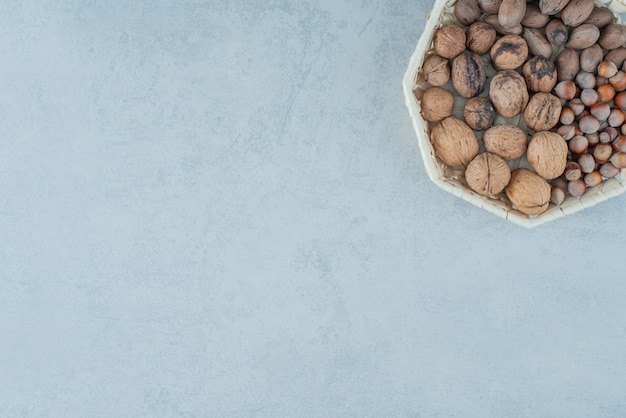 Un panier avec des noix saines sur fond de marbre. photo de haute qualité