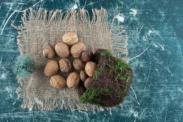 Un panier avec des noix saines et un petit arbre de noël sur un sac. photo de haute qualité