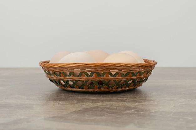 Panier d'oeufs blancs sur table en marbre.