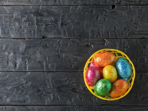 Panier avec des oeufs colorés sur une table rustique noire
