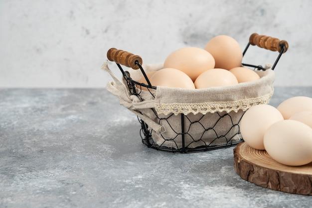 Panier d'oeufs crus frais biologiques placés sur une surface en marbre.