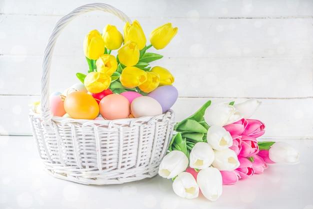 Panier avec oeufs de pâques et bouquet de fleurs de tulipes printanières.