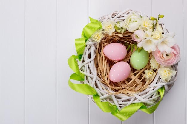 Panier d'oeufs de pâques avec des fleurs