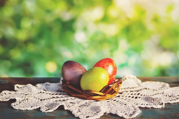Panier d'oeufs de pâques sur des nappes rustiques blanches sur une vieille table vintage aux beaux jours. le petit-déjeuner est servi pour pâques dans le jardin verdoyant du printemps.