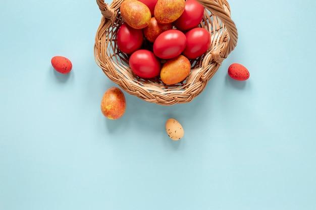 Panier avec des œufs peints en jaune et rouge