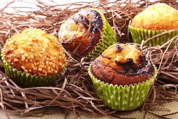 Panier en osier avec assortiment de délicieux muffins maison aux raisins secs et au chocolat.