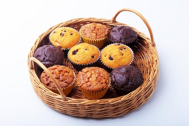 Panier en osier avec assortiment de délicieux petits gâteaux faits maison avec des raisins secs et du chocolat.