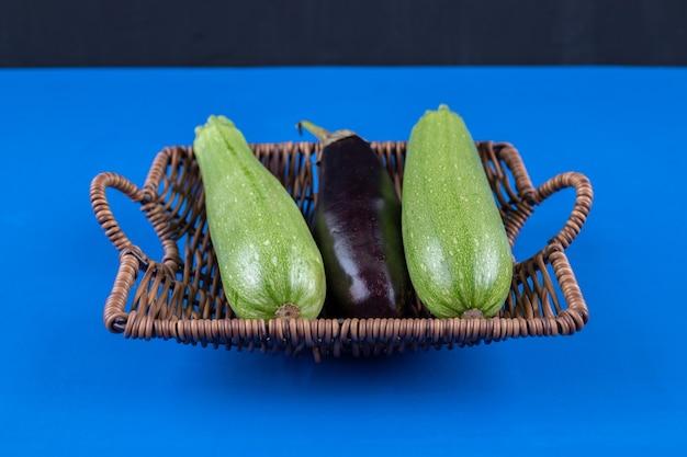 Panier en osier d'aubergines et de courgettes sur une surface bleue